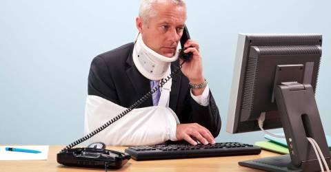Gewonde zakenman met arm in mitella en nekbrace zit achter zijn computer aan zijn bureau aan de telefoon